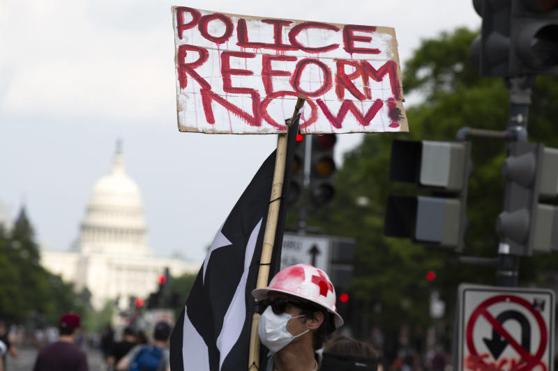 A demonstrator holds a placard, with the US Capitol in the background, during a march on Pennsylvania Ave against racism and police brutality, in Washington, DC on June 6, 2020. - Demonstrations are being held across the US following the death of George Floyd on May 25, 2020, while being arrested in Minneapolis, Minnesota. (Photo by Jose Luis Magana / AFP) (Photo by JOSE LUIS MAGANA/AFP via Getty Images)