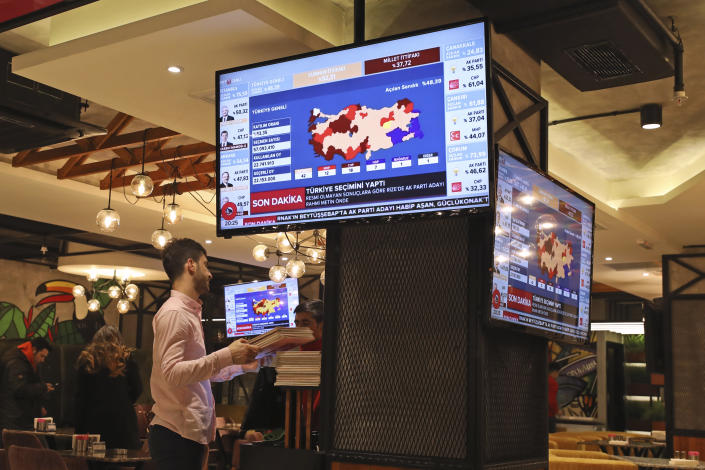 TV coverage of the local elections is seen on screens in a restaurant in Istanbul, Sunday, March 31, 2019. Mayoral elections are underway in 30 large cities in Turkey along with other municipal races Sunday that are seen as a barometer of President Recep Tayyip Erdogan's popularity amid a sharp economic downturn in the nation straddling Europe and Asia. (AP Photo/Emrah Gurel)