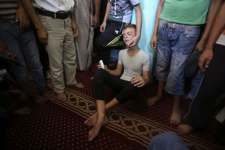 A Palestinian reacts during the funeral of three senior Hamas commanders, who were killed in an Israeli air strike, at a mosque in Rafah in the southern Gaza Strip August 21, 2014. REUTERS/Ibraheem Abu Mustafa