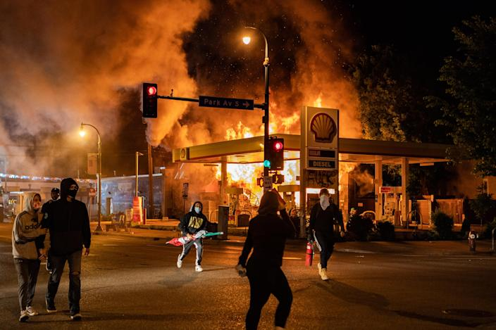 MINNEAPOLIS, MN - MAY 29: Protesters walk past a gas station on the corner of Park Ave S and E. Lake St that is on fire on Friday, May 29, 2020, in Minneapolis, MN. Protests in the wake of the death of George Floyd while in police custody swept country overnight Thursday. (Photo by Salwan Georges/The Washington Post via Getty Images)