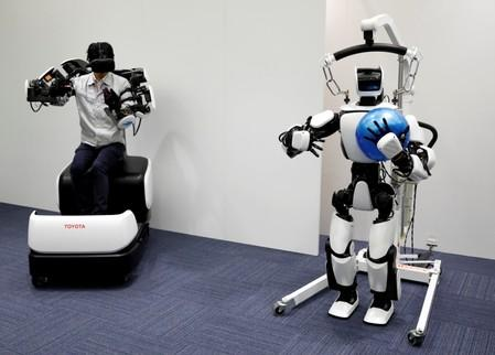 An employee of Toyota Motor Corp. demonstrates T-HR3 humanoid robot which will be used to support the Tokyo 2020 Olympic and Paralympic Games, during a press preview in Tokyo