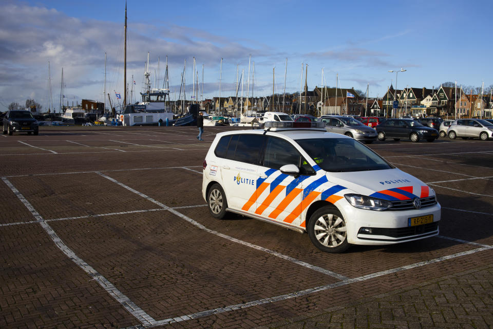 A police vehicle is parked in the harbor near a torched coronavirus testing facility in the Dutch fishing village of Urk, Sunday, Jan. 24, 2021. It was set ablaze Saturday night by rioting youths protesting on the first night of a nation-wide curfew. (AP Photo/Peter Dejong)