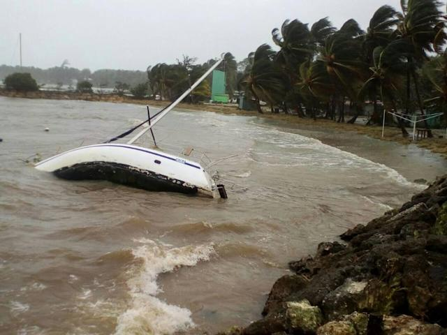 <p>A boat lays on its side off the shore of Sainte-Anne on the French Caribbean island of Guadeloupe, early Tuesday, Sept. 19, 2017, after the passing of Hurricane Maria. (Photo: Dominique Chomereau-Lamotte/AP) </p>