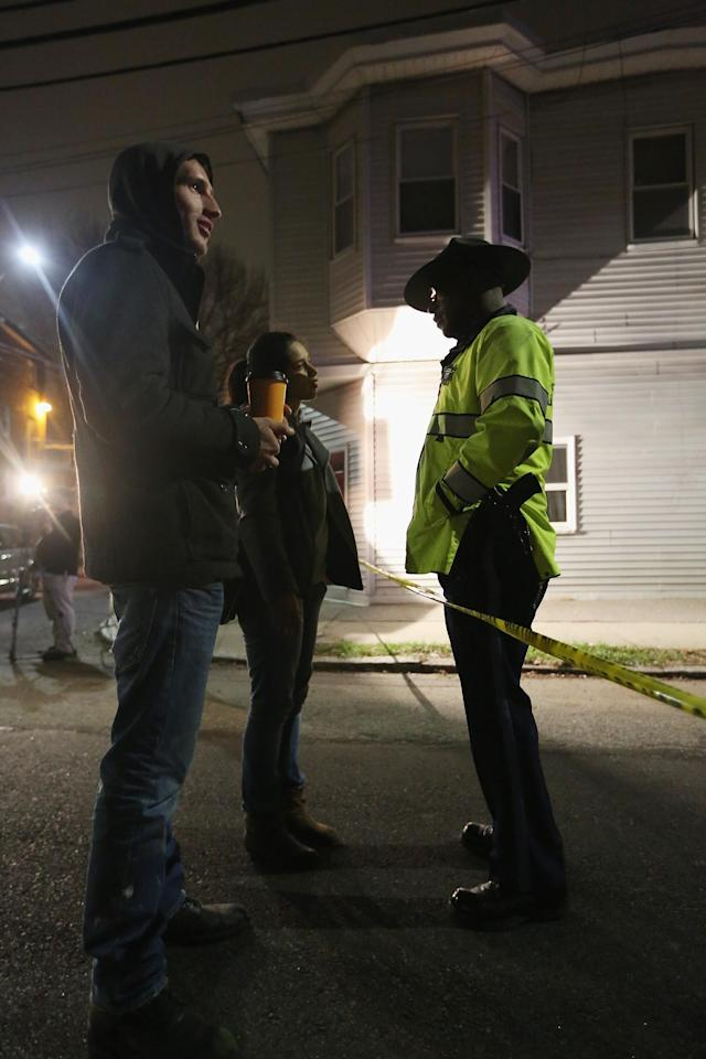 WATERTOWN, MA - APRIL 19: A woman asks a police officer when she will be allowed back to her home in a cordoned off area on April 19, 2013 in Watertown, Massachusetts. Earlier, a Massachusetts Institute of Technology campus police officer was shot and killed late Thursday night at the school's campus in Cambridge. A short time later, police reported exchanging gunfire with alleged carjackers in Watertown, a city near Cambridge. According to reports, one suspect has been killed during a car chase and the police are seeking another - believed to be the same person wanted in connection with the deadly bombing at the Boston Marathon earlier this week. (Photo by Mario Tama/Getty Images)