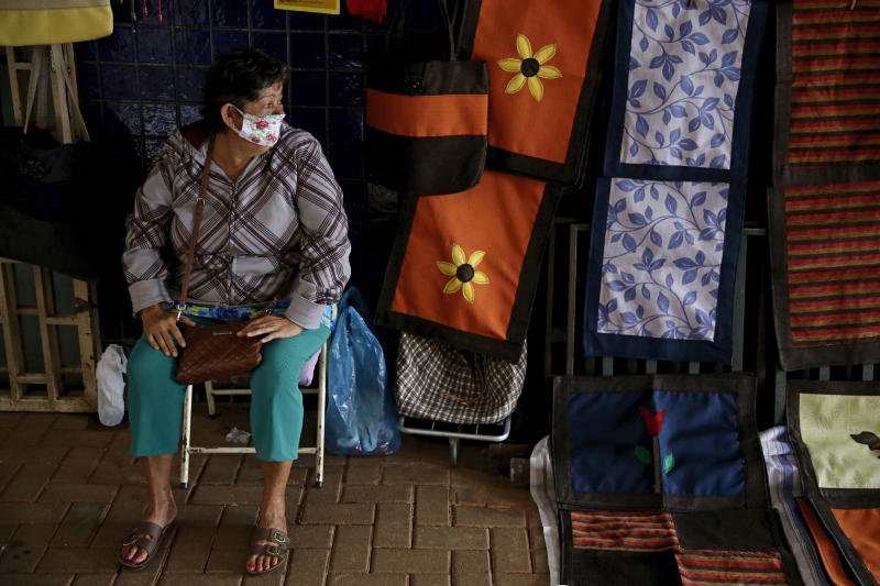 A vendor wearing a face mask sits at her street side clothing shop in Brasilia, Brazil, Monday, May 18, 2020. Starting Monday, the city government authorized the opening of some commerce amid the COVID-19 pandemic. (AP Photo/Eraldo Peres)