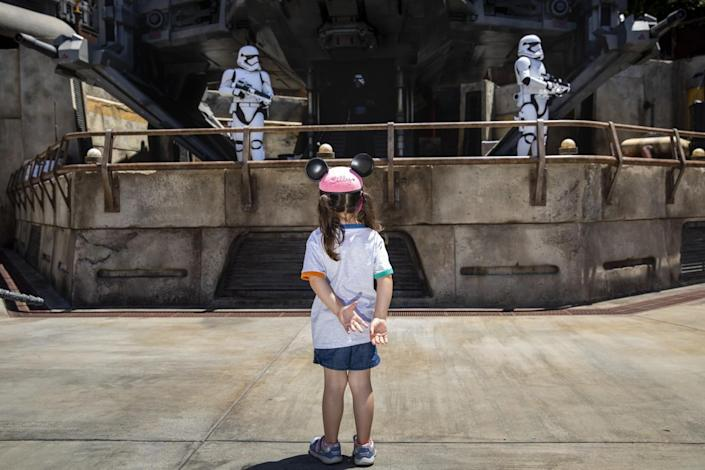 A girl in mouse ears watches two stormtrooper characters behind a railing.