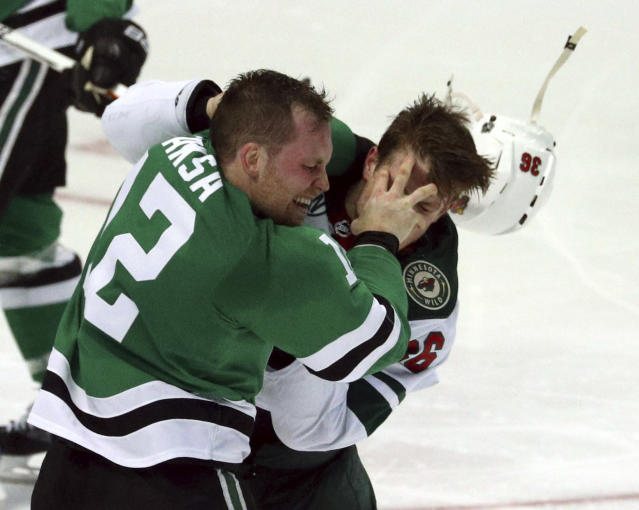 Dallas Stars center Radek Faksa (12) and Minnesota Wild defenseman Nick Seeler (36) fight a second time in the second period of an NHL hockey game Saturday, April 6, 2019, in Dallas. (AP Photo/Richard W. Rodriguez)