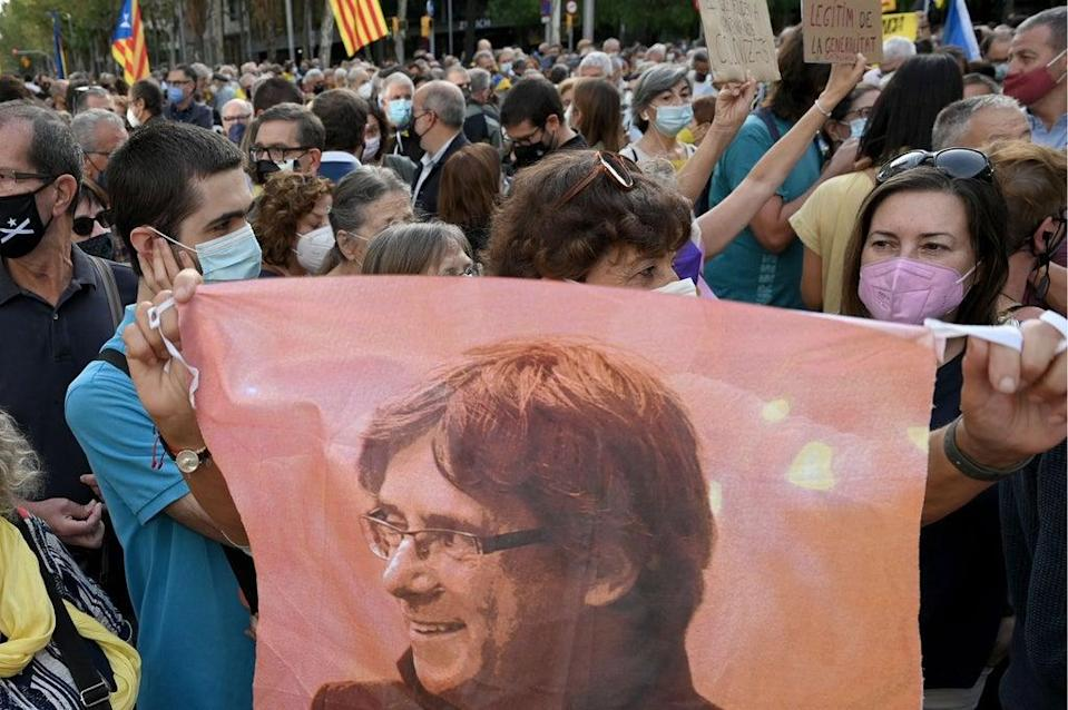 A demonstrator holds a portrait of Carles Puigdemont during a protest in front of the Italian consulate in Barcelona on Friday  (AFP via Getty Images)