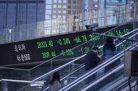People wearing masks, following the coronavirus disease (COVID-19) outbreak, are seen near an electronic board showing Dow Jones and S&P 500 stock indexes, at the Lujiazui financial district in Shanghai