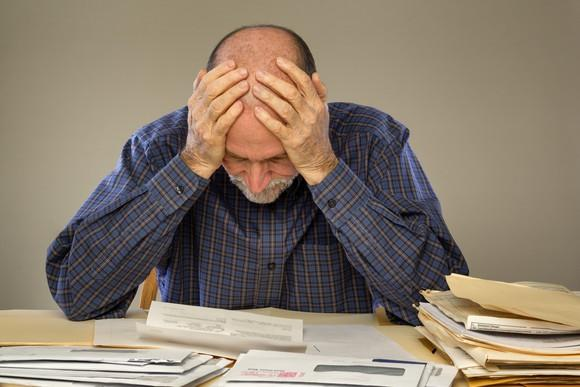 Senior man holding his head while looking at paperwork