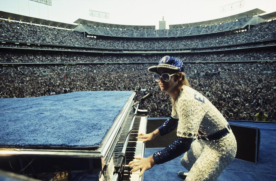 Elton John performing while wearing a jeweled baseball outfit