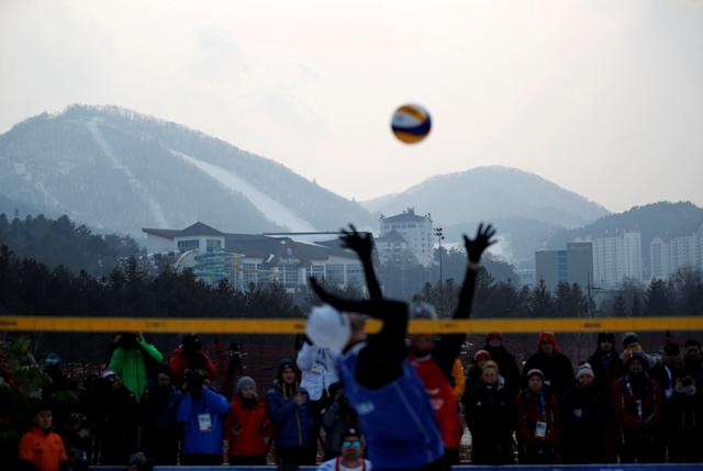 Pyeongchang 2018 Winter Olympics - Pyeongchang - South Korea – February 14, 2018. Snow-covered slopes are seen in the background as players play during an event promoting the Snow Volleyball hosted by the International Volleyball Federation (FIVB) and European Volleyball Confederation (CEV). REUTERS/Kim Hong-Ji