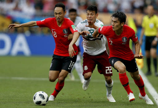 South Korea's Moon Seon-min, left, and LeeYong, right, challenge for the ball with Mexico's Hirving Lozano during the group F match between Mexico and South Korea at the 2018 soccer World Cup in the Rostov Arena in Rostov-on-Don, Russia, Saturday, June 23, 2018. (AP Photo/Eduardo Verdugo)
