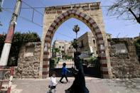 People walk past Qasr al-Basha, where Napoleon Bonaparte reportedly stayed, in Gaza City on April 21, 2021