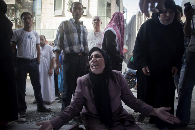 A woman cries near the body of her brother in front of Dar El Shifa hospital in Aleppo, Syria, Tuesday, Sept. 25, 2012. Over the past few months, rebels have increasingly targeted security sites and symbols of regime power in a bid to turn the tide in Syria's 18-month conflict, which activists say has left some 30,000 people dead.(AP Photo/Manu Brabo)