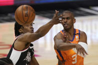Phoenix Suns guard Chris Paul, right, passes while under pressure from Los Angeles Clippers guard Terance Mann during the first half in Game 3 of the NBA basketball Western Conference Finals Thursday, June 24, 2021, in Los Angeles. (AP Photo/Mark J. Terrill)