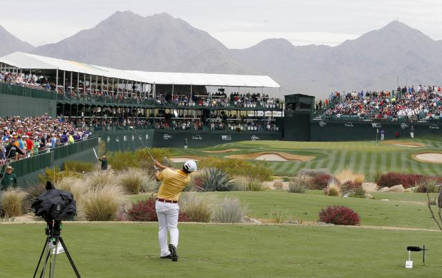 Surrounded by spectators, Ki Taek Lee hits his tee shot on the 16th hole during the second round of the Phoenix Open golf tournament on Friday, Jan. 31, 2014, in Scottsdale, Ariz. (AP Photo/Ross D. Franklin)