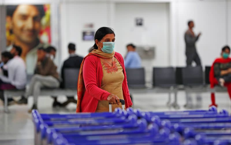 A passenger wearing a protective mask walks inside an airport terminal following an outbreak of the coronavirus disease (COVID-19), in New Delhi
