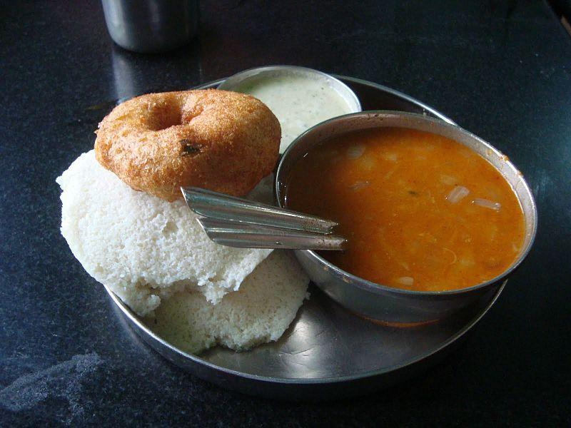 """<p>A delicious preparation of toor dal & vegetables, a staple across South Indian homes. To make sambar, pressure cook one cup toor dal with turmeric powder & enough water. When cool, mash it well. Add salt, one cubed carrot, few ladies fingers & 2 lengthwise slit drumsticks. When the vegetables are half cooked, add one cubed potato, sambar powder to taste & 1 tsp tamarind juice & cook till done. Prepare tempering with 1 tsp oil, hing, sliced small onions, 1-2 red chilies & curry leaves. Pour over the sambar before serving. """"Creative Commons Awesome idly-vada-sambhar """" by Hrish Thota is licensed under CC BY 2.0 </p>"""