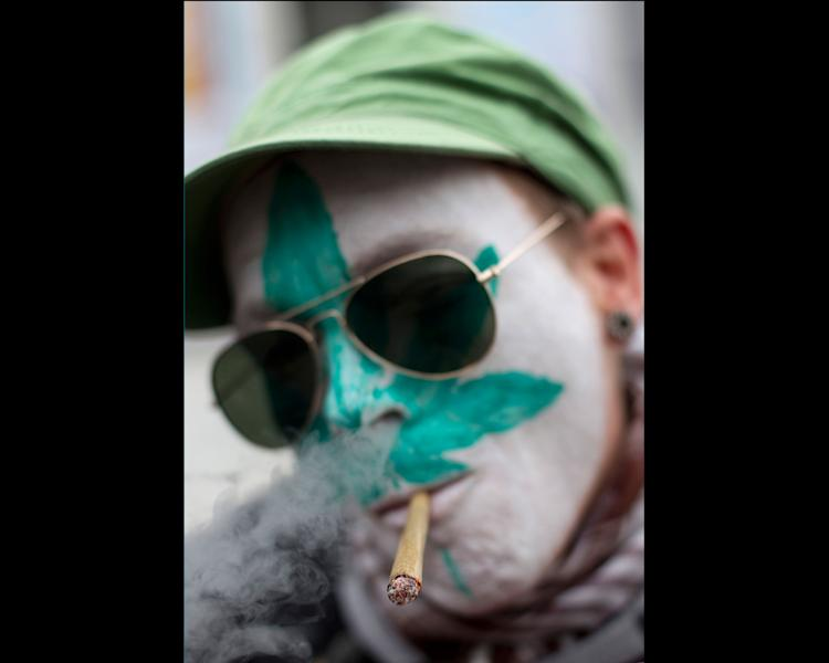 """FILE - In this Friday April 20, 2012 file photo a protestor from Belgium with a marijuana leaf painted on his face smokes a marijuana joint in Amsterdam during a protest against a government plan to stop foreigners from buying marijuana in the Netherlands. A Dutch judge has upheld the government's plan to introduce a """"weed pass"""" on Friday, April 27, 2012, to prevent foreigners from buying marijuana in coffee shops. A lawyer for coffee shop owners says he will file an urgent appeal against Friday's ruling that clears the way for the introduction of the pass in southern provinces on May 1. (AP Photo/Peter Dejong, File)"""