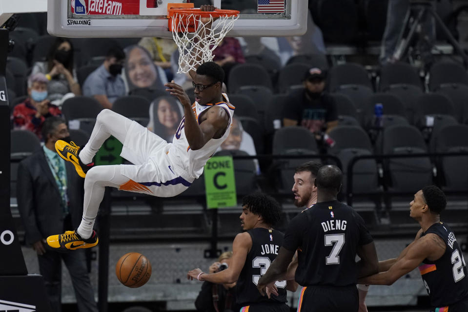 Phoenix Suns forward Jalen Smith (10) hangs on the rim as he scores against the Phoenix Suns during the second half of an NBA basketball game in San Antonio, Sunday, May 16, 2021. (AP Photo/Eric Gay)