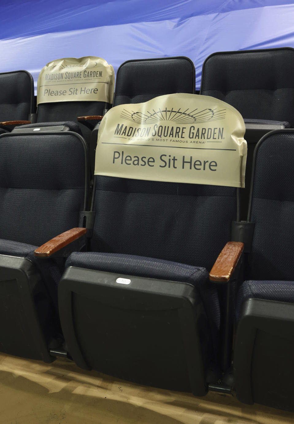 Seats are earmarked for fans at future games prior to the NHL hockey game between the New York Rangers and the Boston Bruins at Madison Square Garden Wednesday, Feb. 10, 2021, in New York. New York State announced today that arenas can re-open on Feb. 23 at 10% occupancy. (Bruce Bennett/Pool Photo via AP)