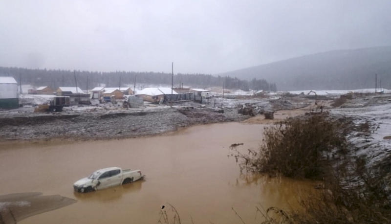 In this image made from video provided by Russian Emergency Situations Ministry press service, a view after the collapse during heavy rain occurred early Saturday near the village of Shchetinkino, in the Krasnoyarsk region about 3,400 Km (2,100 miles) east of Moscow, Russia, Saturday, Oct. 19, 2019.  Russian emergency officials say at least 15 people are dead after a dam at a Siberian gold mine collapsed and water flooded two workers' dormitories,13 people were unaccounted for, Russian news agencies reported. (Russian Ministry of Emergency Situations press service via AP)