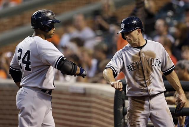 New York Yankees' Brett Gardner, right, fist-bumps teammate Robinson Cano after he scored a run against the Baltimore Orioles on Cano's ground out in the first inning of a baseball game, Wednesday, Sept. 11, 2013, in Baltimore. (AP Photo/Patrick Semansky)