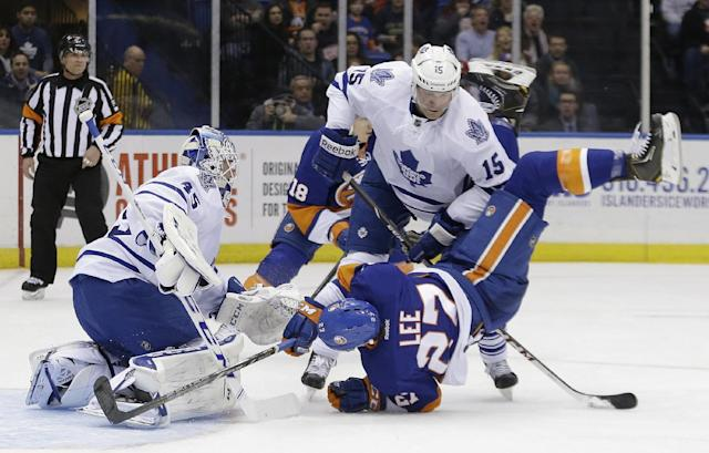 Toronto Maple Leafs' Paul Ranger (15) checks New York Islanders' Anders Lee (27) in front of Jonathan Bernier (45) during the second period of an NHL hockey game Thursday, Feb. 27, 2014, in Uniondale, N.Y. (AP Photo/Frank Franklin II)
