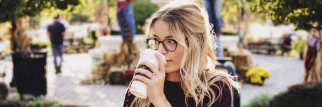 Woman drinking coffee in an outdoor courtyard.