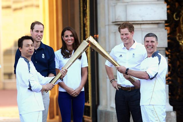 Prince William, Duke of Cambridge, Catherine, Duchess of Cambridge and Prince Harry watch Wai-Ming hand over the London 2012 Olympic Torch to John Hulse during a visit to Buckingham Palace during Day 69 of the London 2012 Olympic Torch Relay on July 26, 2012 in London, England. The Olympic flame is making its way through the capital on the penultimate day of its journey around the UK before arriving in the Olympic Stadium on Friday evening for the Olympic games' Opening Ceremony. (Photo by Ian West - WPA Pool/Getty Images)