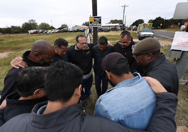 <p>A group of 12 pastors from local churches, pray beside a memorial service for victims of the mass shooting that killed 26 people in Sutherland Springs, Texas on Nov. 8, 2017. (Photo: Mark Ralston/AFP/Getty Images) </p>