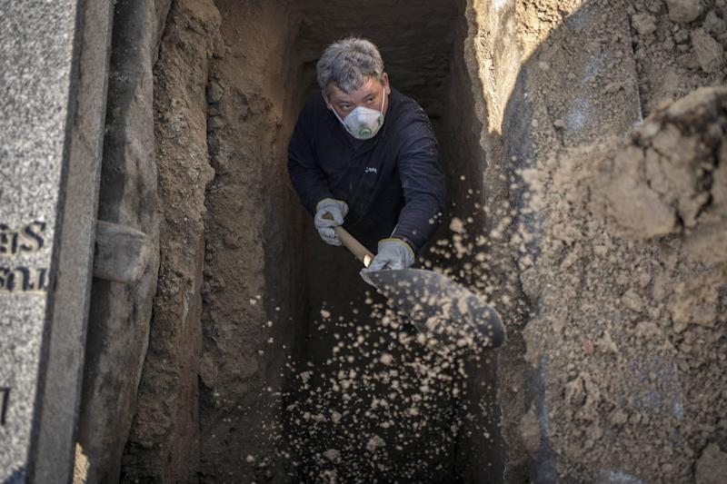 SPAIN: An undertaker prepares a grave at the Almudena cemetery in Madrid.