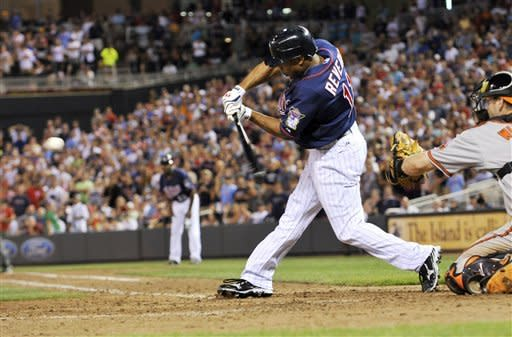 Minnesota Twins' Ben Revere hits an RBI single off Baltimore Orioles pitcher Pedro Strop in the seventh inning of a baseball game, Tuesday, July 17, 2012, in Minneapolis. Catching is Orioles' Matt Wieters. (AP Photo/Jim Mone)