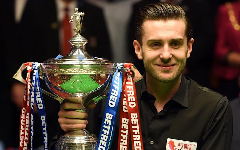 Mark Selby lifts the trophy after winning back-to-back world snooker championships at the Crucible - AFP