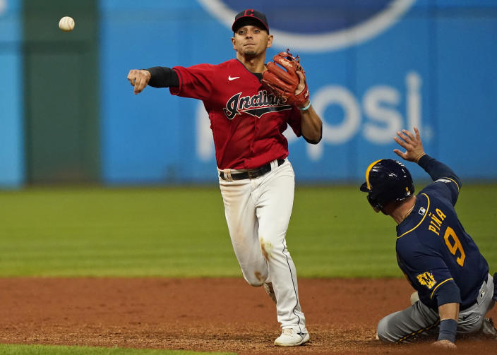 Cleveland Indians' Andres Gimenez, left, gets Milwaukee Brewers' Manny Piña out at second base in the eighth inning of a baseball game, Friday, Sept. 10, 2021, in Cleveland. Daniel Vogelbach was out at first base for a double play. (AP Photo/Tony Dejak)