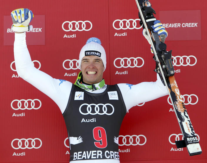 Christof Innerhofer, of Italy, raises his arms on the podium after winning the men's World Cup downhill ski race in Beaver Creek, Colo., on Friday, Nov. 30, 2012. (AP Photo/Alessandro Trovati)