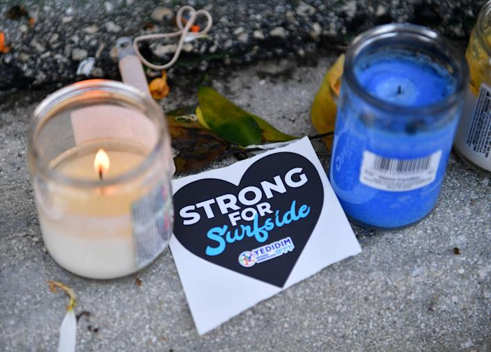 Surfside Strong stickers and candles are among the items left at a memorial wall as recovery efforts continue at the Champlain Towers South condominium in Florida.
