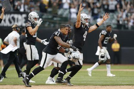 Sep 30, 2018; Oakland, CA, USA; Oakland Raiders quarterback Derek Carr (4) reacts with teammates after the Raiders made a field goal to win the game against the Cleveland Browns in overtime at Oakland Coliseum. Mandatory Credit: Cary Edmondson-USA TODAY Sports