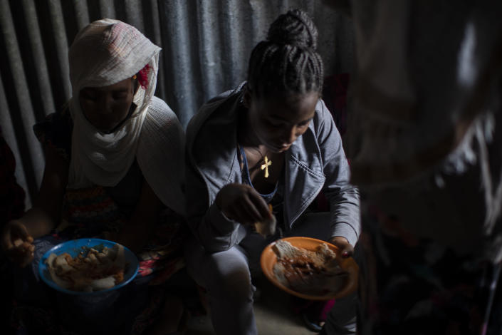 Displaced Tigrayan women, one wearing an Ethiopian Orthodox Christian cross, sit in a metal shack to eat food donated by local residents at a reception center for the internally displaced in Mekele, in the Tigray region of northern Ethiopia, on Sunday, May 9, 2021. (AP Photo/Ben Curtis)