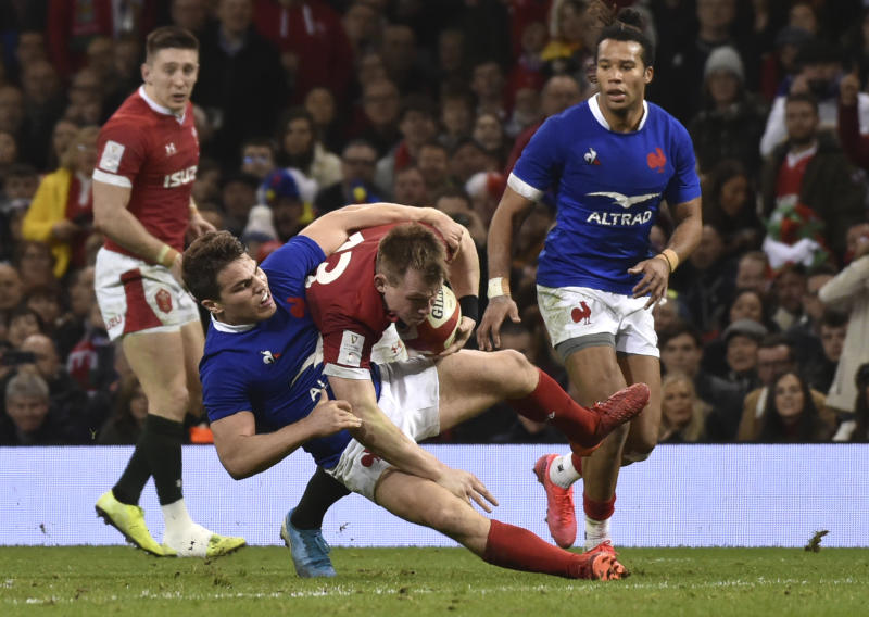 Wales Nick Tompkins is tackled by France's Antoine Dupont during the Six Nations rugby union international between Wales and France at the Principality Stadium in Cardiff, Wales, Saturday, Feb. 22, 2020. (AP Photo/Rui Vieira)