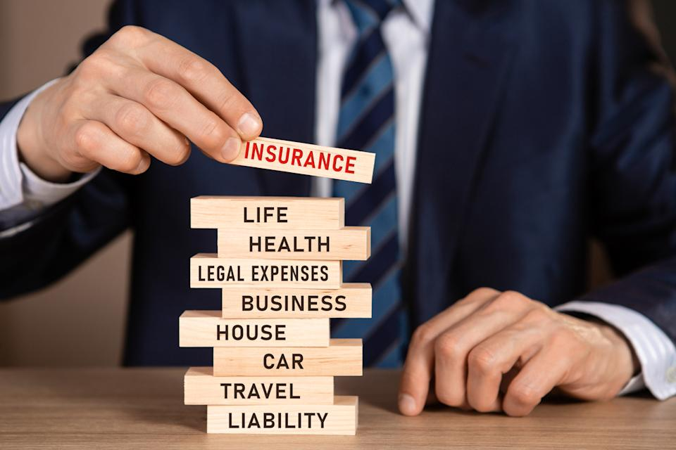 A stack of wooden blocks with words: life, health, legal expenses, business, house, car, travel, liability. Source: Getty Images