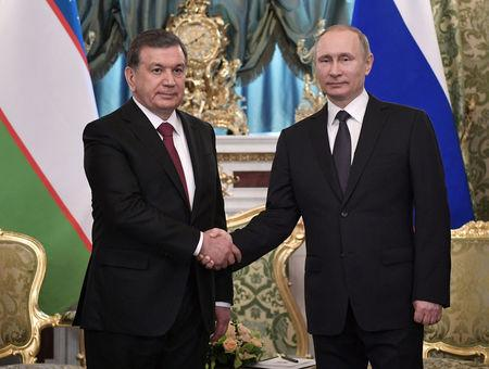 Russian President Putin and Uzbek President Mirziyoyev shake hands during their meeting in Moscow, Russia