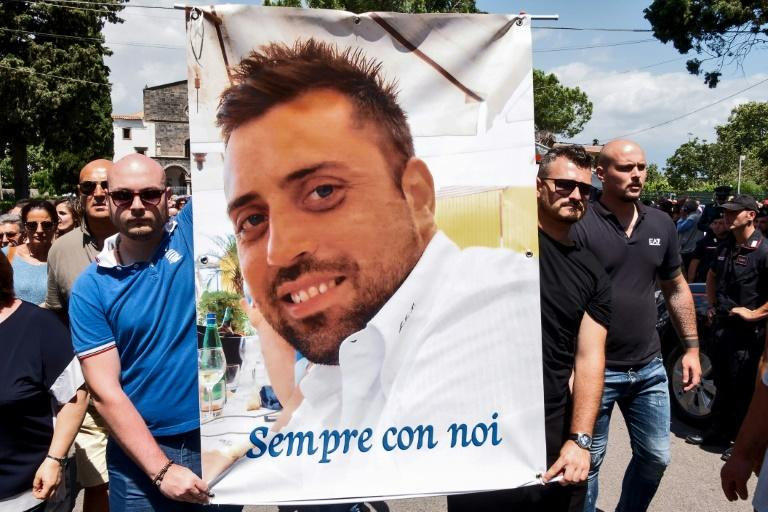 """People carry a banner bearing the photo of Carabinieri officer Mario Cerciello Rega and the slogan """"Forever with us"""""""