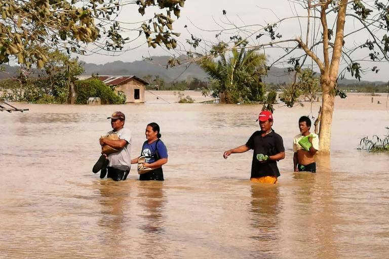 Residents wade through a highway flooded by typhoon Phanfone in Ormoc City, Leyte province