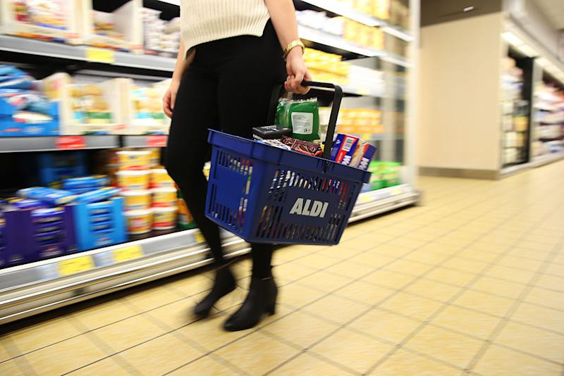 A customer carrying an Aldi Stores Ltd. branded basket walks through one of the company's food stores in Sydney, Australia, on Thursday, June 25, 2015. Australia's biggest supermarkets are losing favor with debt investors as a challenge from German discounter Aldi intensifies competition. Photographer: Brendon Thorne/Bloomberg