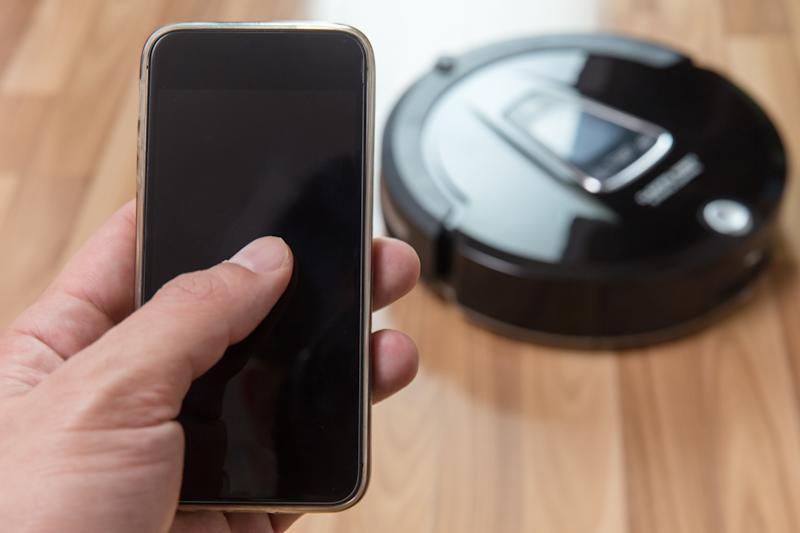 A hand holding a smartphone controlling a robotic vacuum cleaner.