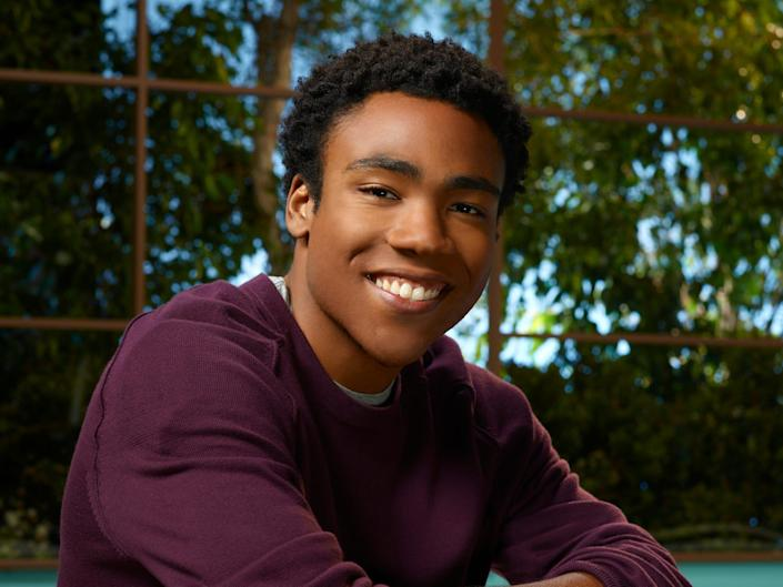 """Donald Glover as Troy in season two of """"Community."""" He is smiling with his arms crossed and wears a purple shirt and jeans."""