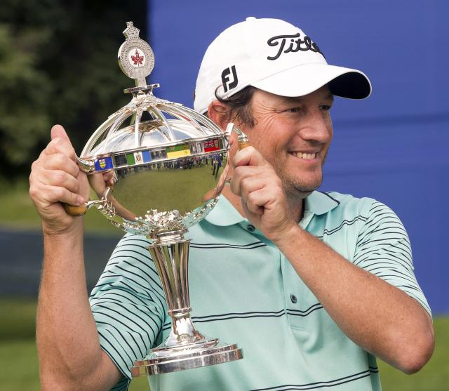 Tim Clark, from South Africa, holds his Canadian Open Championship trophy after final round play at the Canadian Open golf championship, Sunday, July 27, 2014 at Royal Montreal golf club in Montreal.(AP Photo/The Canadian Press, Ryan Remiorz)