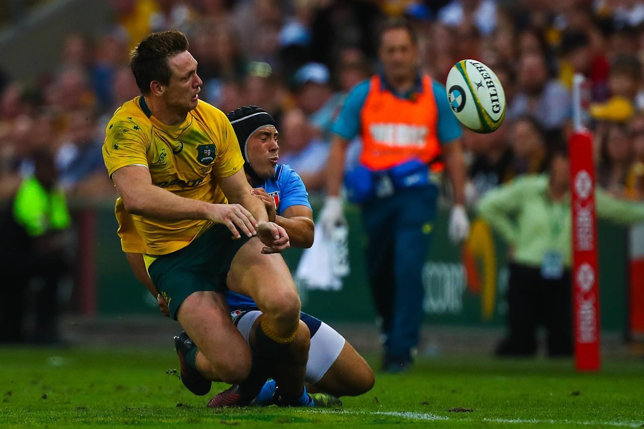 Dane Haylett-Petty of Australia gets a pass away as he is tackled by Pietro Ceccarelli (R) of Italy during the international rugby match between Australia and Italy at Suncorp Stadium in Brisbane on June 24, 2017. (AFP Photo/Patrick HAMILTON)